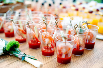 Beautiful row line of different alcohol and non-alcohol cocktails. Snack cocktails with tomato juice and shrimps. Catering table for party.