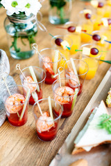Beautiful row line of different alcohol and non-alcohol cocktails. Snack cocktails with tomato juice and shrimps. Vertical photo. Catering table for party.