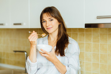 Portrait of charming woman in pajamas standing in the kitchen, holding spoon and bowl with granola - healthy morning breakfast concept.