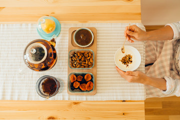 Overhead view of unrecognizable woman having healthy morning breakfast in kitchen at home. Breakfast table with granola, yoghurt, tea, lemon and bowls with almond, dried apricots and jam, kettle.