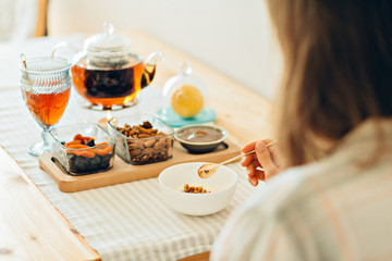Close up of woman's hands holding spoon and bowl with granola - healthy morning breakfast concept. Breakfast table with granola, yoghurt, tea, lemon and bowls with almond, dried apricots, jam, kettle.