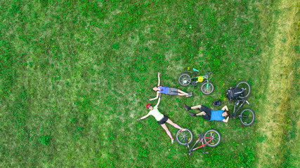 Poster de jardin Cyclisme Family cycling on bikes outdoors aerial view from above, happy active parents with child have fun and relax on grass, family sport and fitness