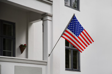 USA flag. American flag displaying on a pole in front of the house. National flag of United States of America waving on a home hanging from a pole on a front door of a building.