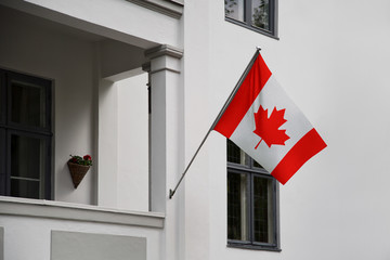 Canada flag. Canadian flag displaying on a pole in front of the house. National flag of Canada waving on a home hanging from a pole on a front door of a building.