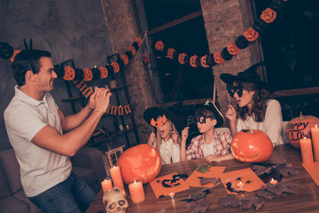 Scary grimaces for the shot! Dad is making memories of creepy night feast indoors with  small siblings, they wearing carnival headwear and eyewear, posing, nicely decorated room, candles flame around
