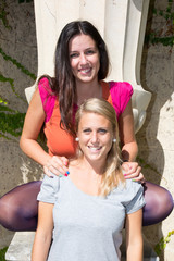 brunette and blond haired girls friends laughing and hug
