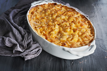 High angel view of a dish of fresh baked macaroni and cheese with table cloth over a rustic dark wood background.