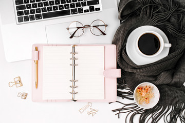 Workspace with laptop, open planner mockup, coffee cup wrapped in scarf,  glasses. Stylish office desk. Autumn or Winter concept.  Flat lay, top view