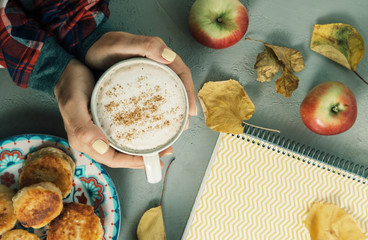 Autumn concept. Woman hands in red shirt with cup of Cappuccino  notebook, leaves, apples, cakes. Top view