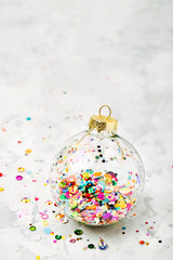Christmas glass transparent ball with colorful sparkle confetti. Christmas concept
