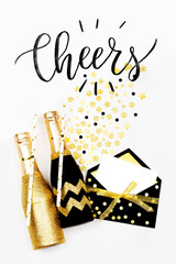 Card with word Cheers with black and gold champagne bottles. Flat lay, top view.