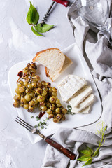 White plate with sliced camembert cheese and baked bunch of green grapes served with bread, wine glass, corkscrew, green leaves, fork on textile over gray texture background. Top view with space
