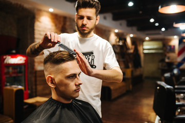 Barber is combing the client's hair comb. Stylish hair styling. Master stylist makes the wedding hairstyle. Cool image. Grunge style with a little noise.