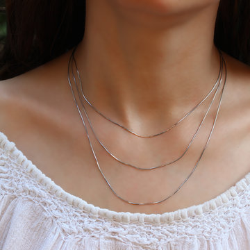 Silver chain at the neck of a woman