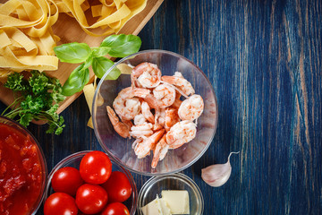 Ingredients ready for preparing pappardelle pasta with shrimp, t