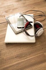 Digital devices and Headphones on a wooden Desktop.