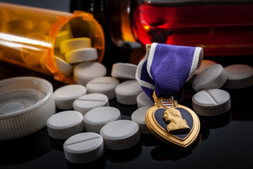 PTSD, veterans reintegration and social issues concept with prescription pills bottle, a flask of alcohol and a medal, illustrating the reality of many veterans that struggle to rejoin civilian life