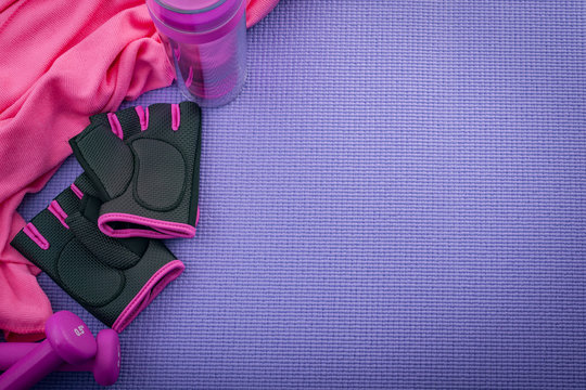 Sport, working out and bodybuilding concept with girly workout equipment like a pink pair of gym gloves, two dumbbells or weights, and a pink towel on a purple yoga mat with copy space