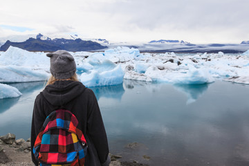 Back view of traveler young girl  with backpack. Glacier lagoon Jokulsarlon, Iceland