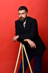 Man with beard wearing classic suit. Macho on photo tripod