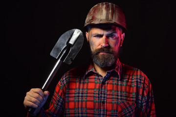 Worker with brutal image wears dirty helmet and holds shovel
