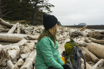 Thoughtful female hiker looking away while sitting on logs at Olympic Coast