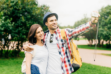 Happy couple having walk in green park, making selfie, embracing each other, spending good time together during their summer vacations. Two tourists photographing on beautiful nature background