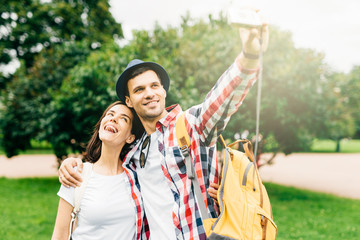 Joyful female and her best friend having excursion in park, making selfie, having happy expressions while hugging. Female and male walking on street. Positive emotions, facial expressions concept