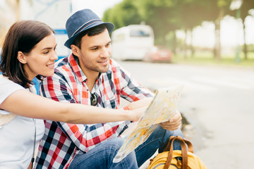 Outdoor portrait of young man and woman sitting together at bench, having rest for minute after long trip across big town, looking in map, pointing or indicating place where they haven`t been