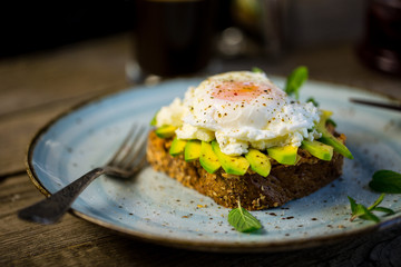 Black bread toast with fried benedict egg, avocado and salmon spread in blue plate with coffee in background, wooden shabby table with coffee pot, glass and books stack