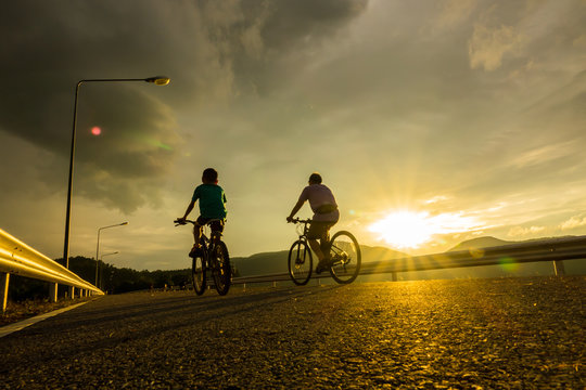 Peple biking on road with sunset silouette background.