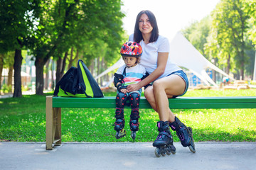 Portait of cute baby boy and his mom wearing inline skates sitting on bench.