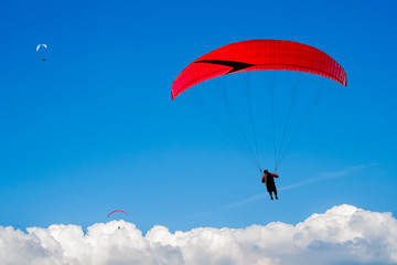 Foto op Aluminium Luchtsport The paraglider hovers in the sky high above the clouds