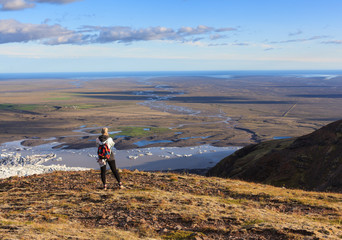 Icelandic adventure. Travel in Iceland. Girl with backpack hiking on mountains