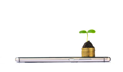 smart phone with stack of coins and seedling on top. business finance concept