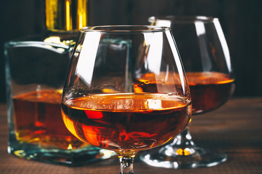 Two glasses of brandy or cognac and bottle on the wooden table.