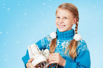 Cheerful little girl in blue warm sweater holding figure skates. White background.