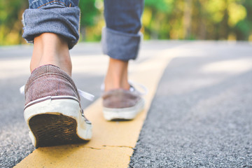 Feet of girl walking in the road and forest background, Relax time on holiday concept travel ,color of vintage tone and soft focus