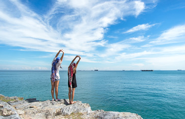 Two traveler young women seeing the beautiful beach and blue sky, so happy and relax.  Travel Concept.