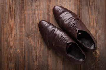 Men's brown shoes on a wooden background