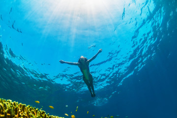 Happy family - girl dive underwater with tropical fishes in coral reef sea pool. Travel lifestyle, water sport outdoor adventure, swimming lessons on summer beach holiday with kids.