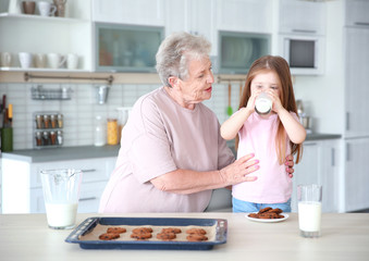 Cute little girl and her grandmother with cookies on kitchen