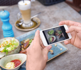 Man photographing tasty food with mobile phone, closeup