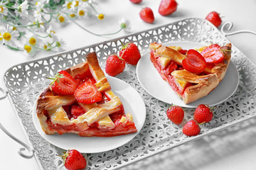 Plates with delicious strawberry pie on tray