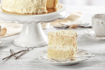 Slice of delicious vanilla cake on wooden table