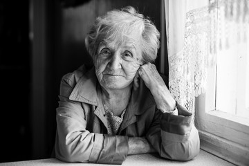 An elderly woman black and white portrait of sitting at the table.
