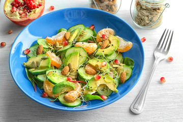 Superfood salad with avocado, tangerine and almond on light background