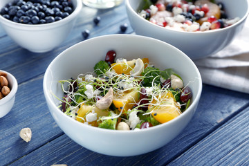 Superfood salad with yellow tomato, broccoli and cashew nuts in white bowl on wooden background