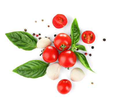 Mozzarella cheese balls, cherry tomatoes and green fresh organic basil isolated on white