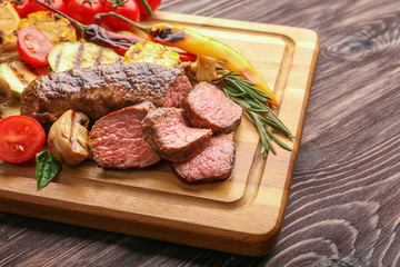 Wall Mural - Tasty meat with vegetables on wooden board